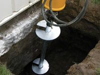 Installing a helical pier system in the earth around a foundation in Waipahu